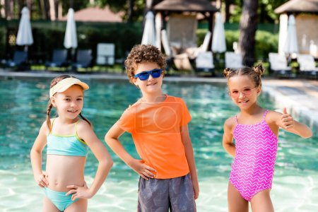 Photo for Friends standing with hands on hips while girl showing thumb up near pool - Royalty Free Image