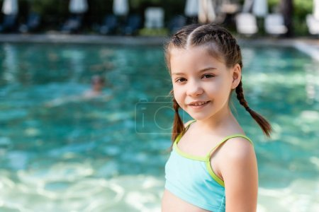 Photo for Girl in swimsuit looking at camera while posing near swimming pool - Royalty Free Image