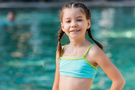 Photo pour Girl in swimsuit looking at camera while posing at resort - image libre de droit
