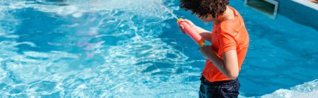 Photo for Panoramic crop of boy playing with water gun near pool - Royalty Free Image