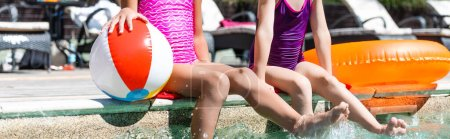 Photo for Cropped view of girls making water splashes with legs while sitting at poolside near inflatable ball and ring, panoramic shot - Royalty Free Image