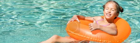 Photo for Horizontal concept of joyful girl showing thumb up while swimming in pool on inflatable ring with closed eyes - Royalty Free Image