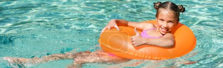 Photo for Horizontal crop of joyful girl showing thumb up while floating in pool on inflatable ring - Royalty Free Image