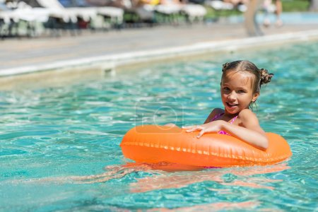 Photo pour Child floating in pool on swim ring and looking at camera - image libre de droit