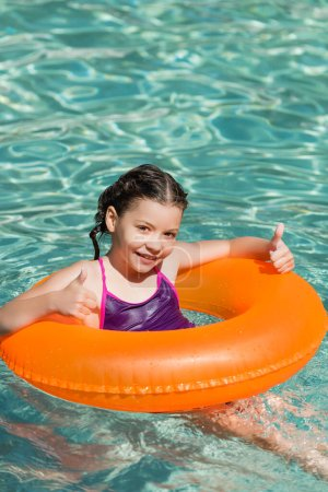 Photo for Joyful kid showing thumbs up while swimming in pool on inflatable ring - Royalty Free Image