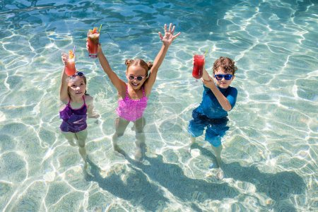 high angle view of children standing in pool and holding fresh fruit cocktails in raised hands