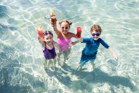 Foto de Vista de ángulo alto de amigos emocionados sosteniendo vasos con cócteles frescos en la piscina - Imagen libre de derechos