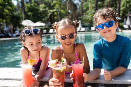 Photo for Joyful friends in sunglasses and swimwear holding fresh fruit cocktails near pool - Royalty Free Image