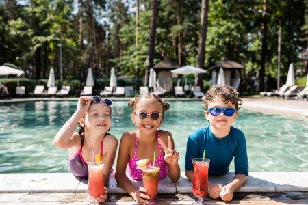Foto de Chica en gafas de sol mostrando gesto de victoria cerca de amigos con cócteles de fruta fresca en la piscina - Imagen libre de derechos