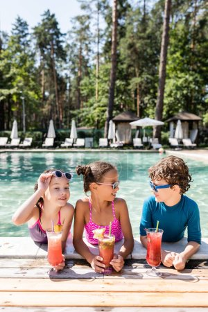 Photo for Joyful girl touching sunglasses while looking at camera near friends with fresh fruit cocktails at poolside - Royalty Free Image