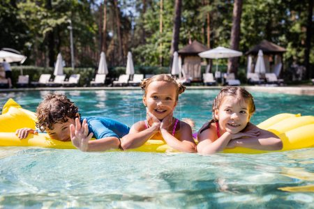 Photo for Joyful boy waving hand at camera while swimming on inflatable mattress with girls - Royalty Free Image