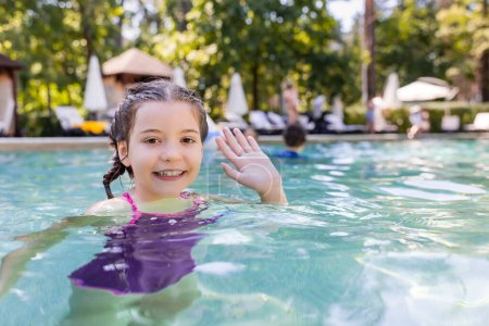 Photo for Joyful girl in swimming pool looking at camera and waving hand - Royalty Free Image