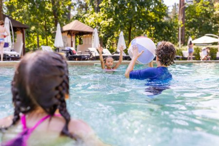 Photo pour Selective focus of friends playing in swimming pool with inflatable ball - image libre de droit