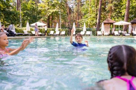 Photo pour Foyer sélectif de garçon et deux filles s'amusant dans la piscine - image libre de droit
