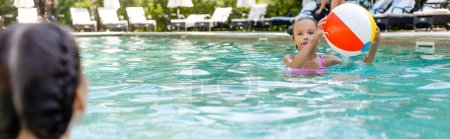 Photo pour Back view of kid near girl holding inflatable ball in swimming pool, panoramic concept - image libre de droit