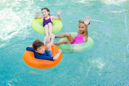 Photo for High angle view of joyful friends waving hands while swimming in pool on inflatable rings - Royalty Free Image
