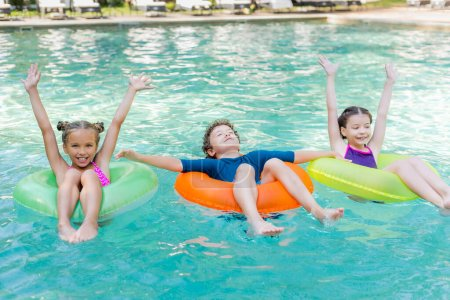 Photo for Joyful girls with hands in air and boy with closed eyes floating in pool on swim rings - Royalty Free Image
