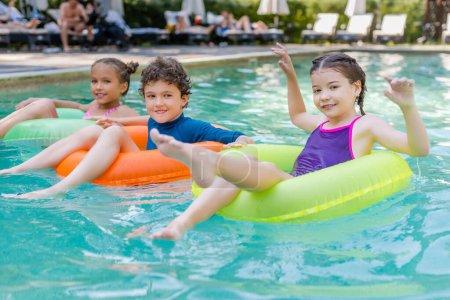 Photo pour Amis joyeux regardant la caméra tout en flottant dans la piscine sur des anneaux de natation multicolores - image libre de droit
