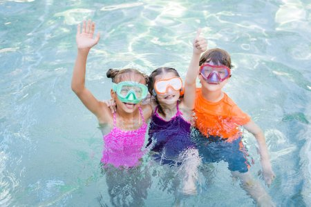 Photo for Friends in swim masks showing thumb up and waving hand while having fun in pool - Royalty Free Image
