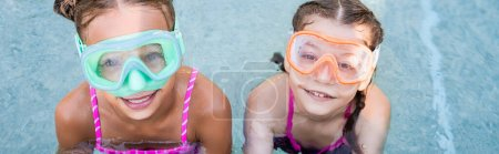 Photo for Overhead view of two girls in swim masks looking at camera near poolside, horizontal crop - Royalty Free Image