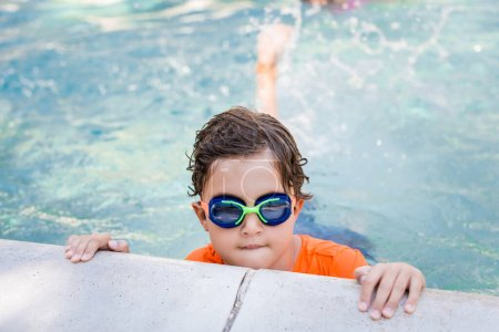 Photo pour Boy wearing swim goggles in water near poolside - image libre de droit