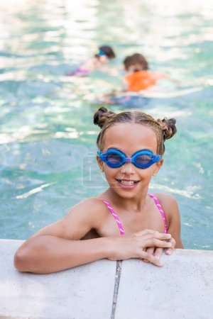 Photo pour Child in swim goggles looking at camera at poolside - image libre de droit
