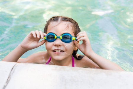 Photo for Girl in pool touching swim goggles while looking at camera - Royalty Free Image