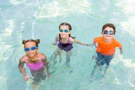 Photo for High angle view of friends in swim goggles looking at camera while spending time in pool - Royalty Free Image