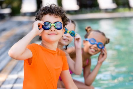 Photo for Selective focus of friends touching swim goggles while looking at camera - Royalty Free Image