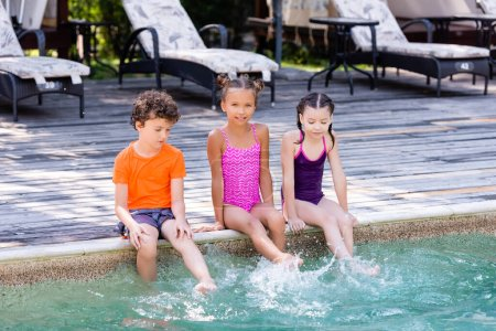 Photo pour Girls in swimsuits and boy in t-shirt sitting on poolside and making water splashes with legs - image libre de droit
