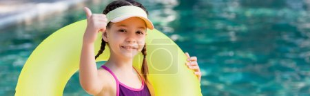 Photo for Panoramic concept of girl in swimsuit and sun visor cap showing thumb up while holding swim ring - Royalty Free Image