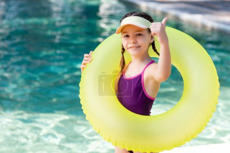 Photo for Girl in swimwear and sun visor cap showing thumb up while holding swim ring near pool - Royalty Free Image