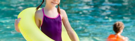 cropped view of girl in swimsuit holding inflatable ring, horizontal image