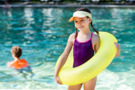 Photo pour Girl in swimsuit and sun visor cap posing with inflatable ring near pool - image libre de droit