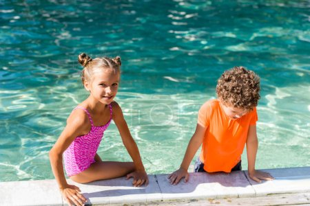 Photo pour Girl in swimsuit looking at camera while sitting on poolside near curly boy in t-shirt - image libre de droit