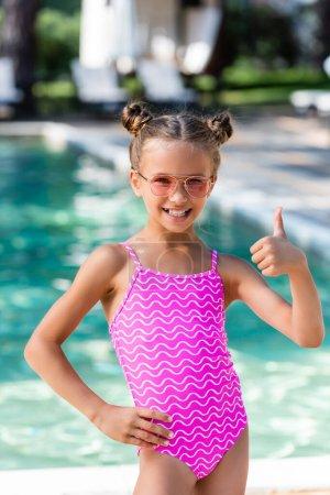 Photo pour Fille en maillot de bain et lunettes de soleil tenant la main sur la hanche et montrant pouce vers le haut - image libre de droit
