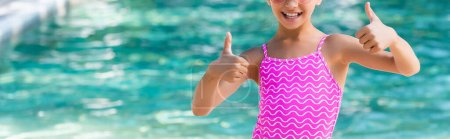 Photo for Cropped view of child in swimsuit showing thumbs up, panoramic shot - Royalty Free Image