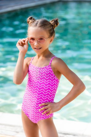 Photo for Child in swimsuit touching sunglasses while posing with hand on hip near pool - Royalty Free Image