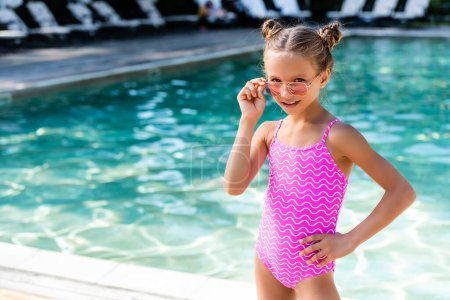 Photo pour Girl in swimsuit touching sunglasses while standing with hand on hip near pool - image libre de droit