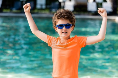 Photo pour Curly boy in orange t-shirt and sunglasses showing winner gesture near pool - image libre de droit