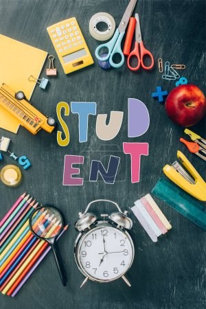 Photo for Top view of frame with apple, toy school bus, vintage alarm clock and school supplies on black chalkboard with student lettering - Royalty Free Image