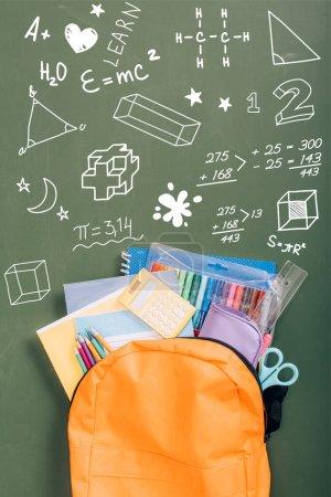 Photo pour Vue du dessus du sac à dos rempli de papeterie scolaire sur un tableau vert avec illustration - image libre de droit