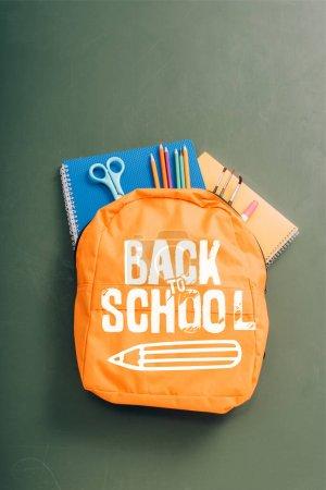 Photo pour Vue du dessus du sac à dos rempli de papeterie scolaire sur un tableau vert avec lettrage de retour à l'école et illustration au crayon - image libre de droit