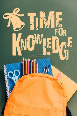 top view of yellow backpack with notebooks, scissors, paintbrushes and color pencils on green chalkboard with time for knowledge lettering