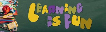 Foto de Plano panorámico de manzana madura, calculadora y papelería de la escuela en pizarra verde con el aprendizaje es divertido letras - Imagen libre de derechos