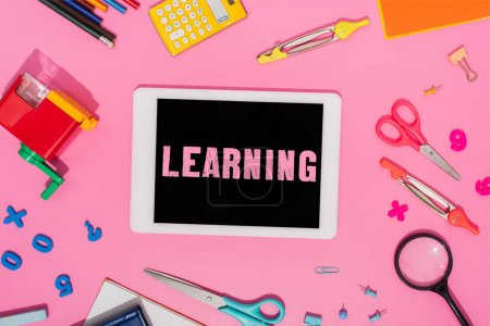 top view of digital tablet with learning lettering on screen near school stationery on pink