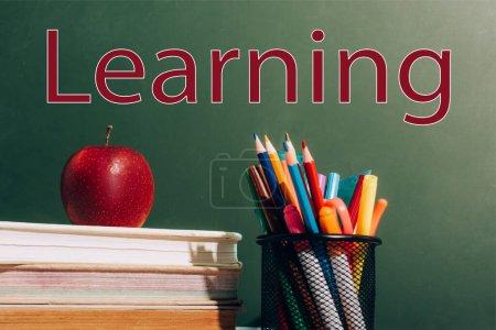 Photo pour Porte-stylo avec crayons de couleur, stylos en feutre et pomme mûre sur des livres près du tableau vert avec lettrage d'apprentissage - image libre de droit