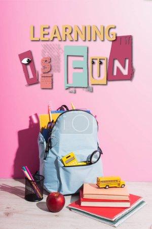 Photo pour Sac à dos scolaire plein de papeterie, porte-stylo, pomme mûre, livres et bus scolaire jouet près de l'apprentissage est lettrage amusant sur rose - image libre de droit