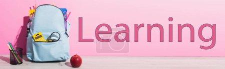 Photo pour Image horizontale du sac à dos bleu avec fournitures scolaires près de pomme entière, porte-stylo avec stylos en feutre et lettrage d'apprentissage sur rose - image libre de droit