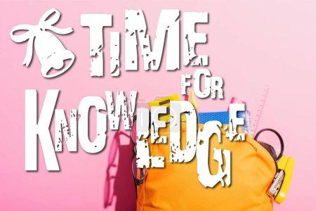 Photo pour Sac à dos jaune emballé avec de la papeterie scolaire et des lunettes près du temps pour le lettrage des connaissances sur rose - image libre de droit
